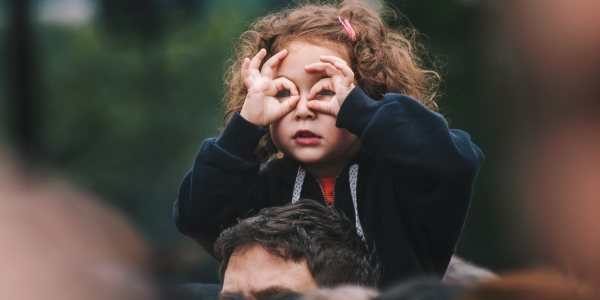 Girl on shoulders looking through her fingers